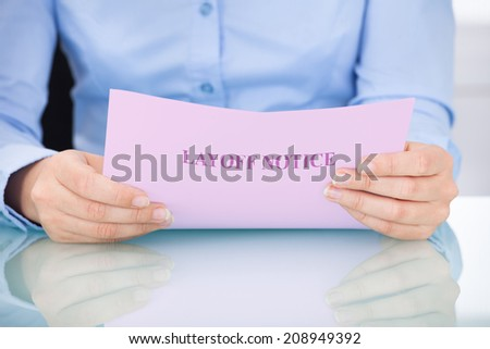 Midsection of businesswoman reading layoff notice at desk - stock photo