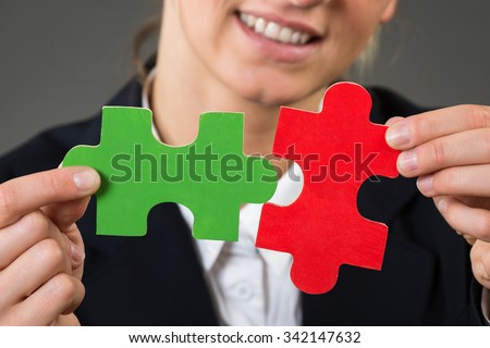 Midsection of businesswoman solving jigsaw puzzle over gray background