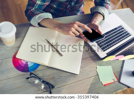 Midsection of creative editor using smartphone and laptop at office - stock photo