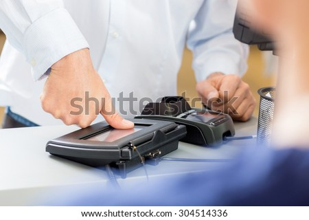 Midsection of customer giving thumb impression to make payment in pharmacy - stock photo