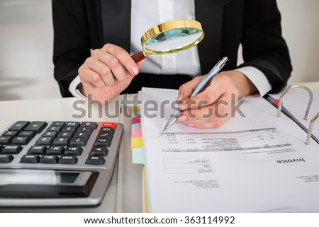 Midsection of female accountant analyzing invoice with magnifying glass at desk in office - stock photo