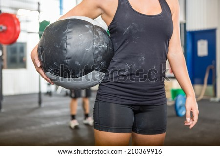 Midsection of female athlete carrying medicine ball at gym - stock photo