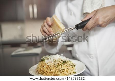 Midsection of female chef grating cheese onto pasta in kitchen