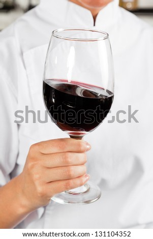 Midsection of female chef holding glass of red wine - stock photo