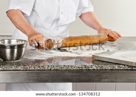 Midsection of female chef rolling dough at industrial kitchen counter - stock photo