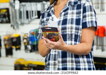 Midsection of female customer scanning product's barcode through mobilephone in hardware store - stock photo