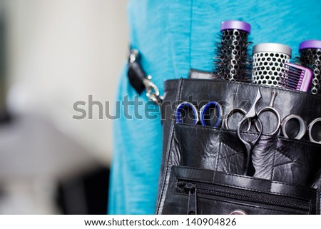 Midsection of female hairdresser with leather tool bag in salon - stock photo
