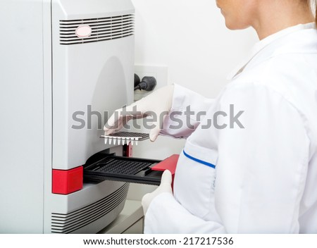 Midsection of female researcher loading analyzer with samples in laboratory - stock photo