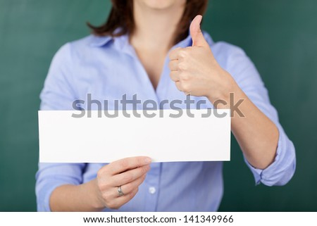 Midsection of female teacher holding blank paper while gesturing thumbs up against chalkboard - stock photo