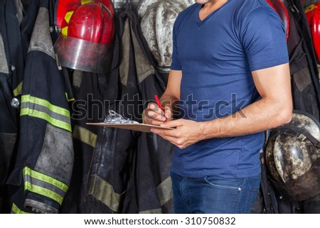 Midsection of fireman writing on clipboard at fire station - stock photo