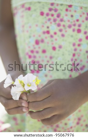Midsection of girl holding flowers - stock photo