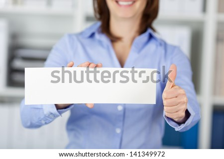 Midsection of happy businesswoman holding blank paper while gesturing thumbs up in office - stock photo