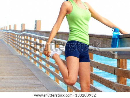 Midsection of healthy young woman stretching her leg during exercise on bridge. Horizontal shot. Pretty mixed racial fitness woman stretching on the boardwalk at Dania Beach in South Florida. - stock photo