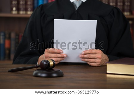 Midsection of judge reading document at desk in courtroom - stock photo