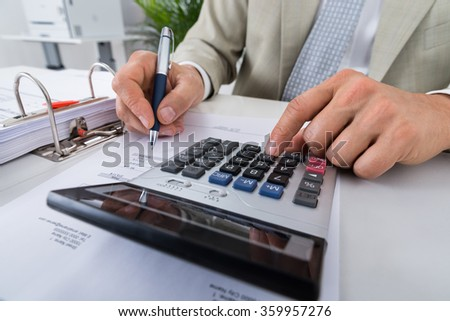Midsection of male accountant calculating bills at desk in office