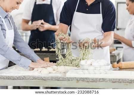 Midsection of male and female chefs preparing pasta in commercial kitchen - stock photo