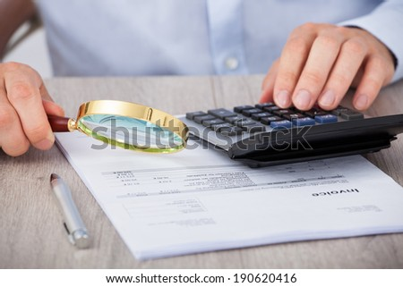 Midsection of male auditor scrutinizing financial documents at desk - stock photo