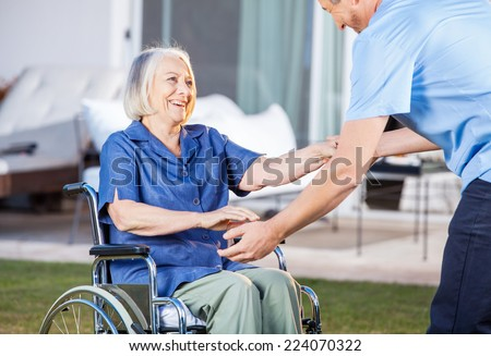 Midsection of male caretaker helping senior woman to get up from wheelchair at nursing home lawn - stock photo