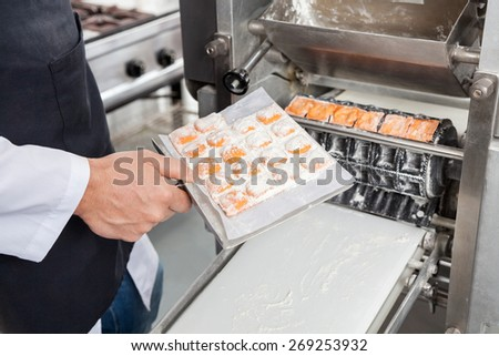 Midsection of male chef processing ravioli pasta in automated machine at commercial kitchen - stock photo
