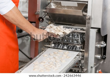 Midsection of male chef removing ravioli pasta from machine at commercial kitchen - stock photo