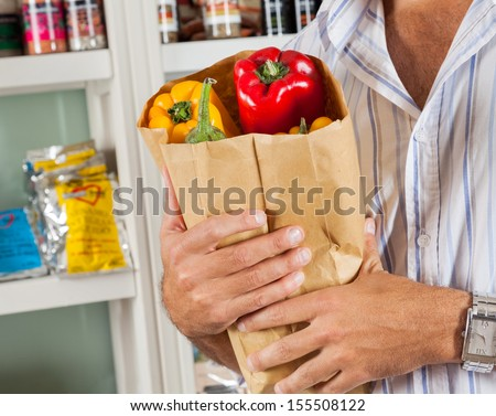 Midsection of male customer holding bag of fresh vegetables in grocery store - stock photo