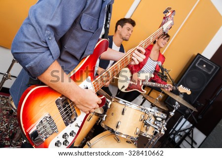 Midsection of male guitarist performing with band in recording studio - stock photo