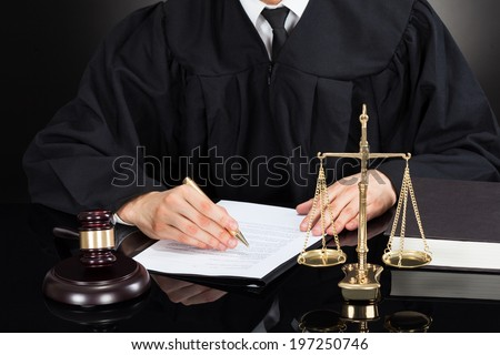 Midsection of male judge writing on paper at desk against black background - stock photo