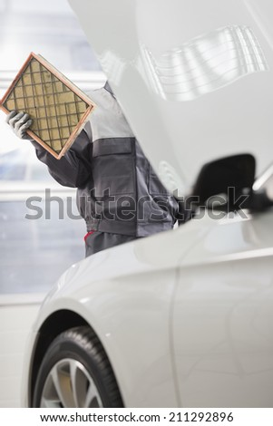Midsection of male maintenance engineer repairing car in automobile store