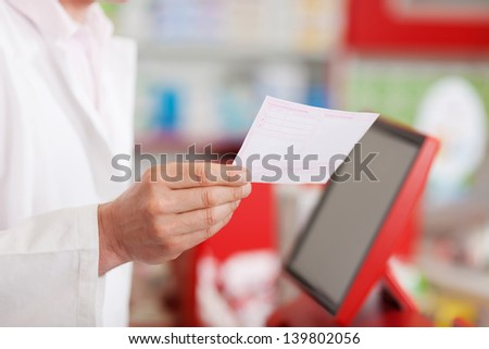 Midsection of male pharmacist holding prescription paper - stock photo