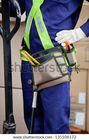Midsection of male using pallet jack in warehouse - stock photo