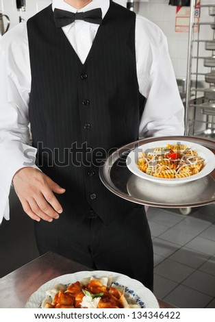 Midsection of male waiter holding dish in restaurant kitchen - stock photo