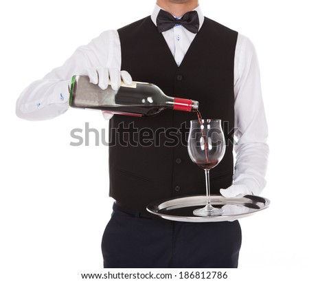 Midsection of male waiter serving red wine in glass against white background - stock photo