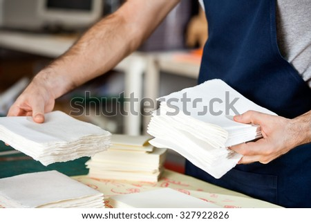 Midsection of male worker stacking papers at table in factory - stock photo