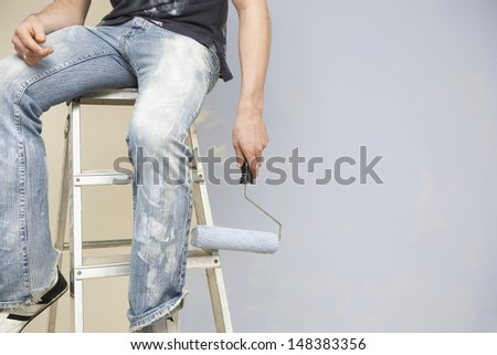 Midsection of man holding paintroller while sitting on stepladder against wall - stock photo