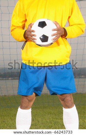 Midsection of man holding soccer ball - stock photo