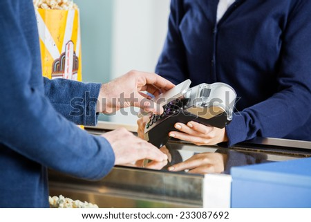 Midsection of man using NFC technology to pay bill at concession counter in cinema - stock photo