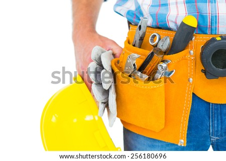 Midsection of manual worker wearing tool belt while holding gloves and helmet on white background - stock photo