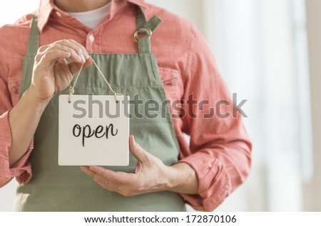 Midsection of mature man showing open sign - stock photo