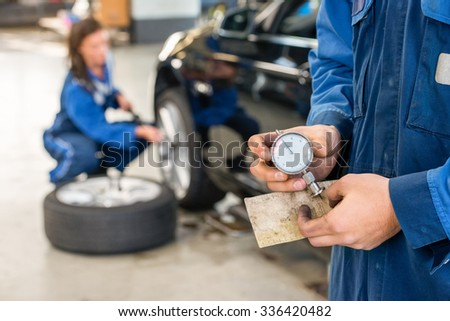 Midsection of mechanic holding analog gauge with colleague repairing car in background at garage - stock photo