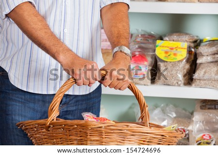 Midsection of mid adult man holding wicker basket in supermarket