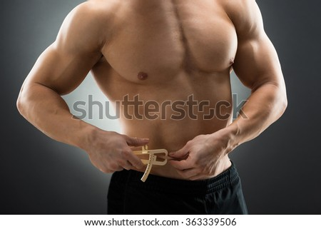 Midsection of muscular man measuring fats with caliper against black background - stock photo