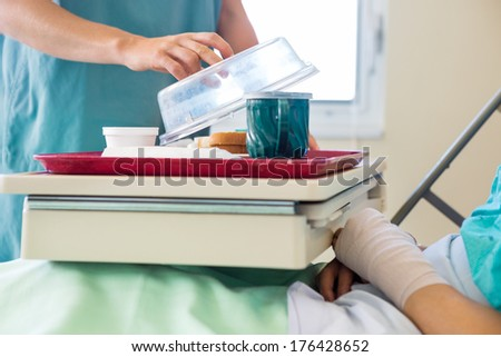 Midsection of nurse lifting cover from tray for male patient in hospital - stock photo