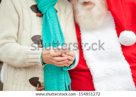 Midsection of Santa Claus with boy using smartphone - stock photo