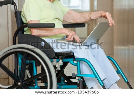 Midsection of senior woman sitting in wheelchair using laptop at hospital - stock photo
