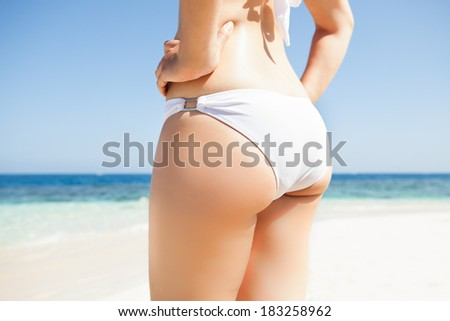 Midsection of sexy young woman in white bikini bottom standing on beach - stock photo