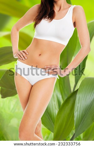 Midsection of slim woman in innerwear standing with hands on hips against leaves - stock photo