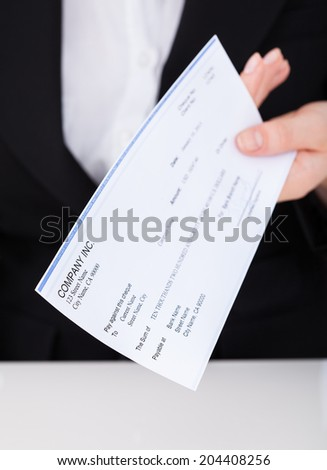 Midsection of smiling businesswoman holding cheque in office - stock photo