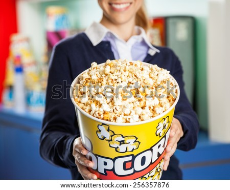 Midsection of smiling female worker offering popcorn bucket at cinema concession stand - stock photo