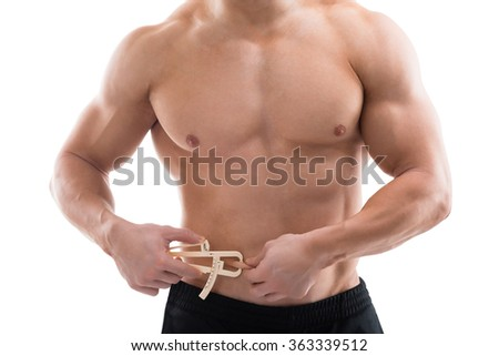 Midsection of strong man measuring fats with caliper against white background