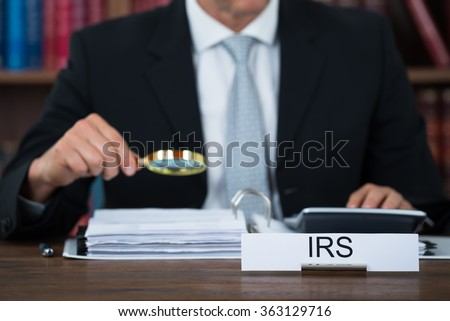 Midsection of tax auditor examining documents with magnifying glass at table in office - stock photo